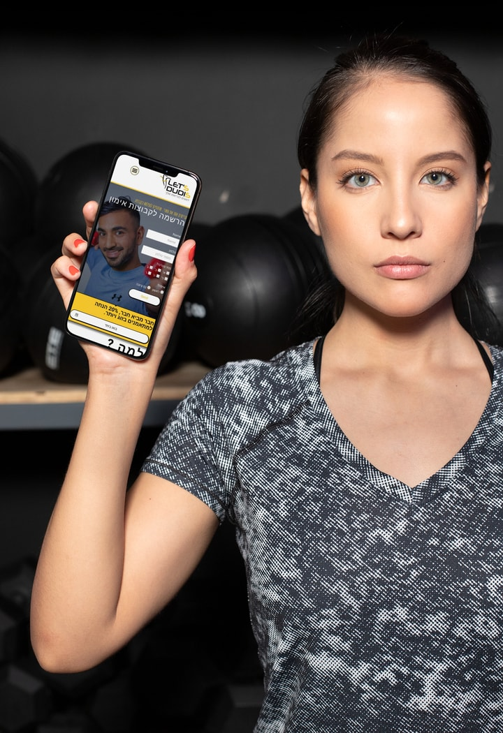 אישה מחזיקה טלפון עם האתר של דודי זצנה מאמן כושר