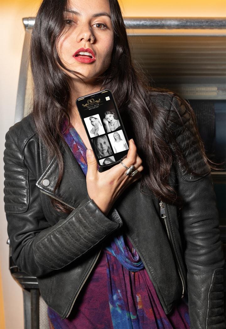 אישה מחזיקה בטלפון עם האתר של סוכנות דוגמנות שרון